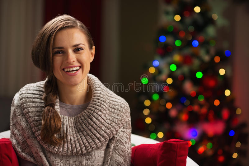 Happy woman and Christmas tree in background. Portrait of happy woman with Christmas tree in background stock photo