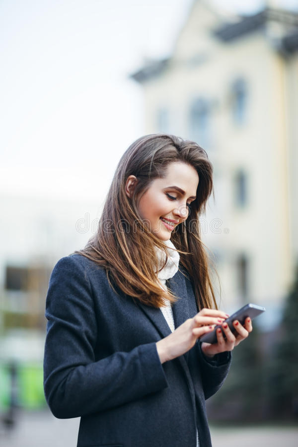 Happy woman on the city street with mobile phone writing sms. Happy beautiful woman on the city street with mobile phone writing sms royalty free stock photos