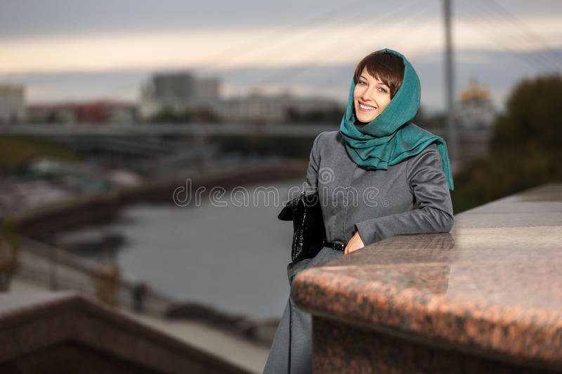 Happy woman in classic coat on the urban backgroun stock photos