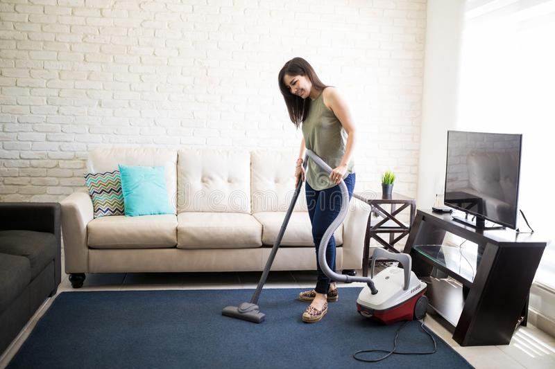 Happy woman cleaning house living room stock photography