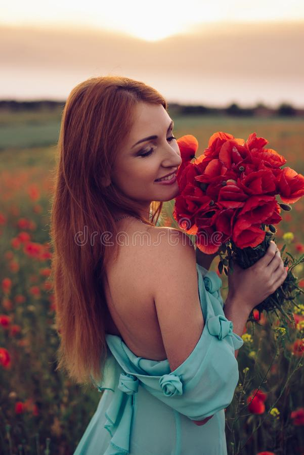 Happy woman with closed eyes holding bouquet of poppies stock image