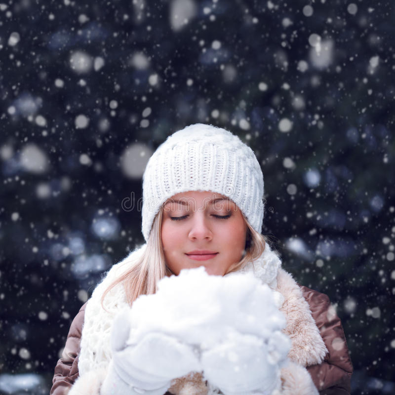 Happy woman with closed eyes holding snow royalty free stock photo