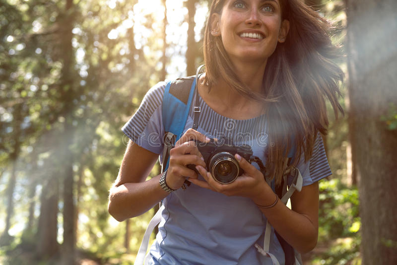 Happy woman closeup with vintage camera walking on hiking trail path in forest woods during sunny day.Group of friends stock images