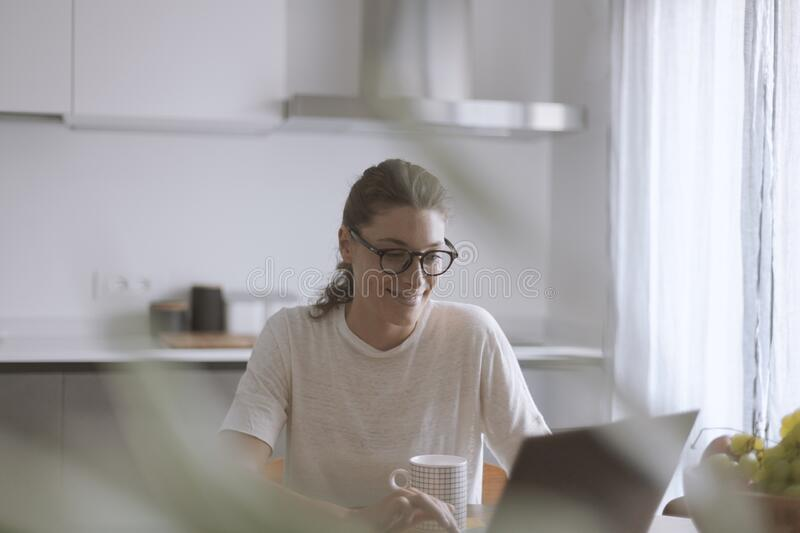 Happy woman connecting with her laptop and drinking coffee royalty free stock photo