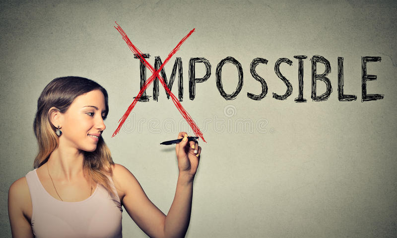 Happy woman converting the word impossible to possible with pen stock photo