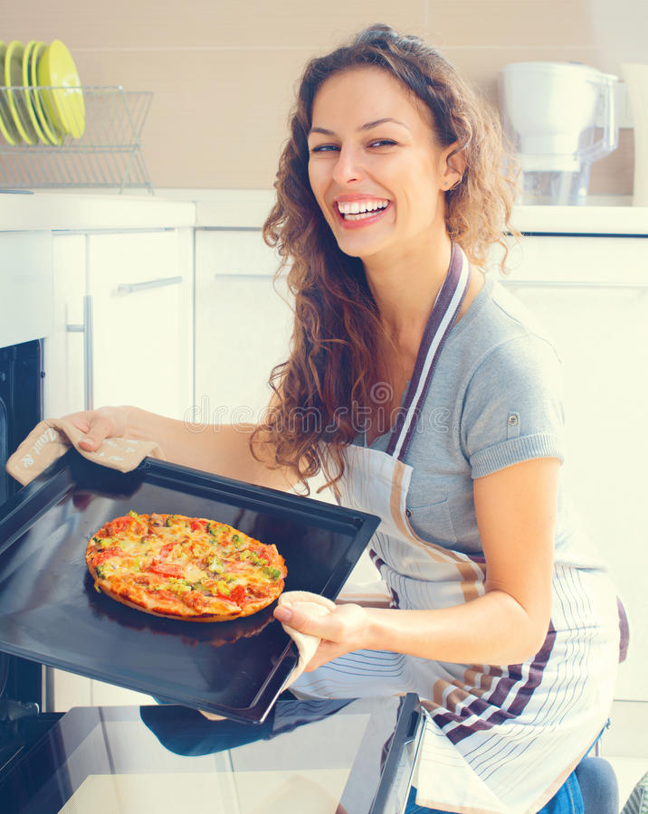 Happy woman cooking pizza at home royalty free stock image