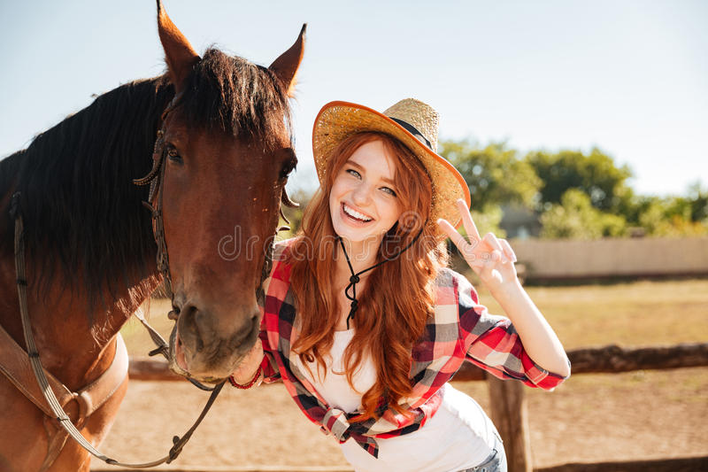 Happy woman cowgirl standing with horse and showing peace sign royalty free stock photo