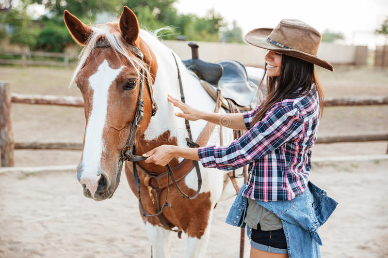 Happy woman cowgirl taking care of her horse on ranch royalty free stock images