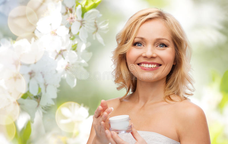 Happy woman with cream jar stock photos