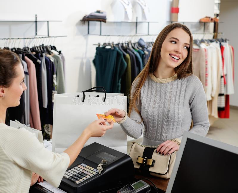 Happy woman customer paying with credit card. Happy women customer paying with credit card in fashion showroom stock image