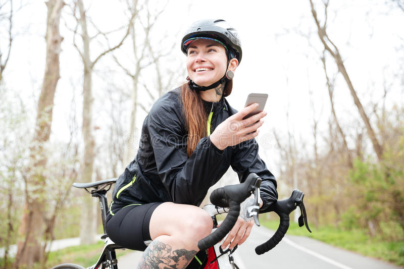 Happy woman in cycling helmet on bicycle using smartphone stock photography