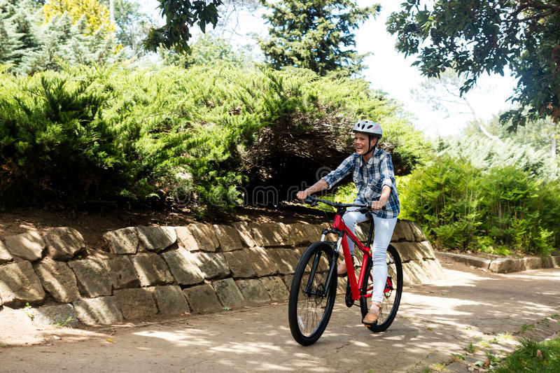 Happy woman cycling in park stock photos