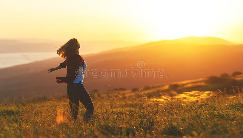 Happy woman dances, jump, rejoices, laughs on sunset in nature. Happy woman with open hands dances, jump, rejoices, laughs on sunset in nature stock images