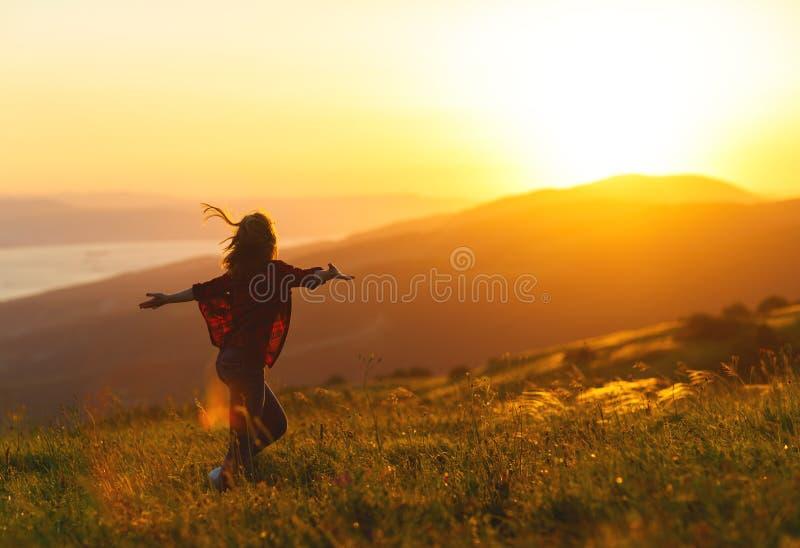Happy woman dances, rejoices, laughs on sunset in nature. Happy woman with open hands dances, rejoices, laughs on sunset in nature royalty free stock images