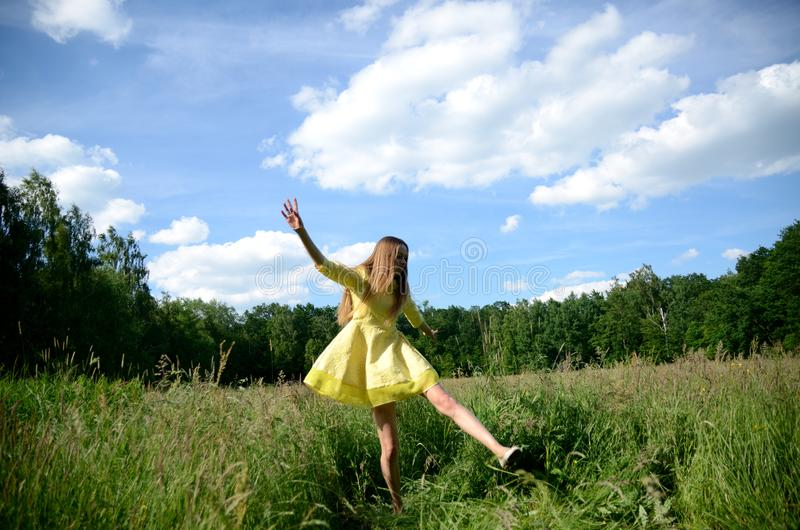 Happy woman dancing on the grass stock photography