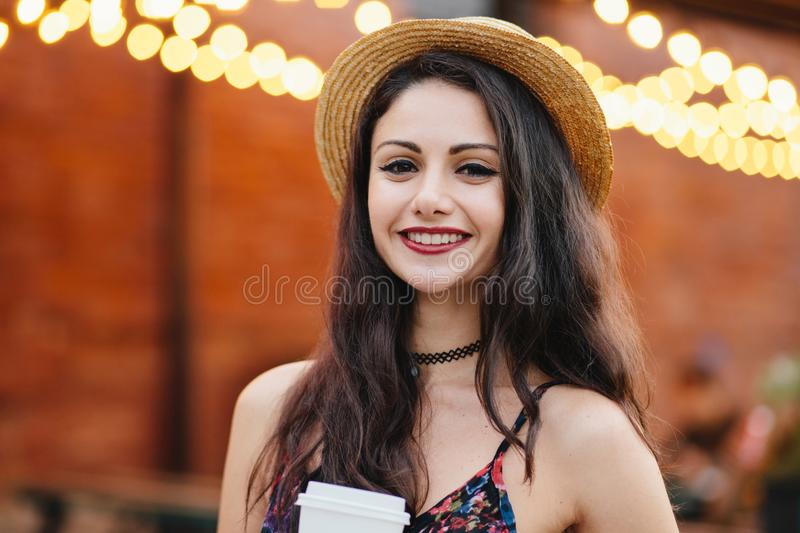 Happy woman with dark hair, charming eyes and gentle smile wearing straw hat, having summer vacations, spending free time at terra stock photography