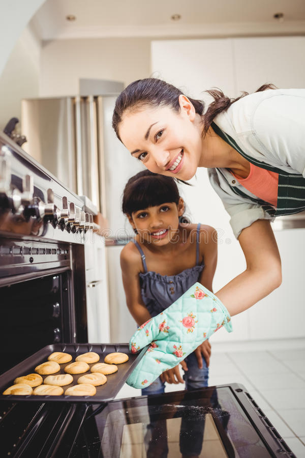 Happy woman with daughter placing cookies in oven stock images