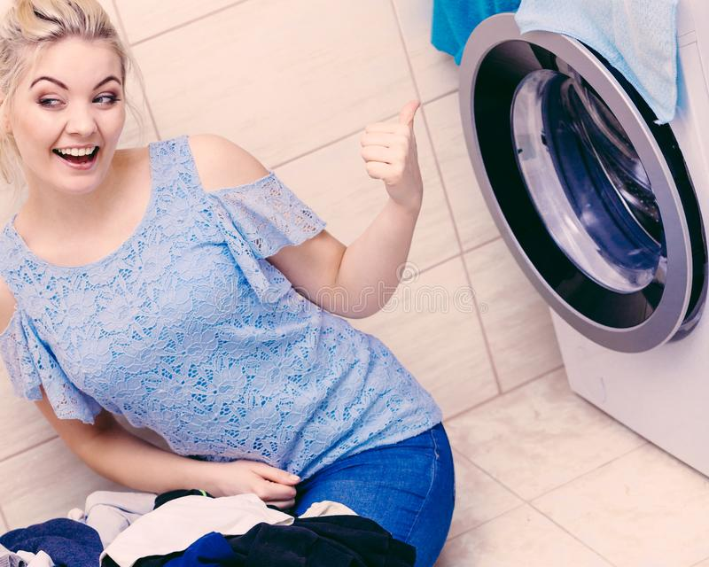 Happy woman washing laundry stock images