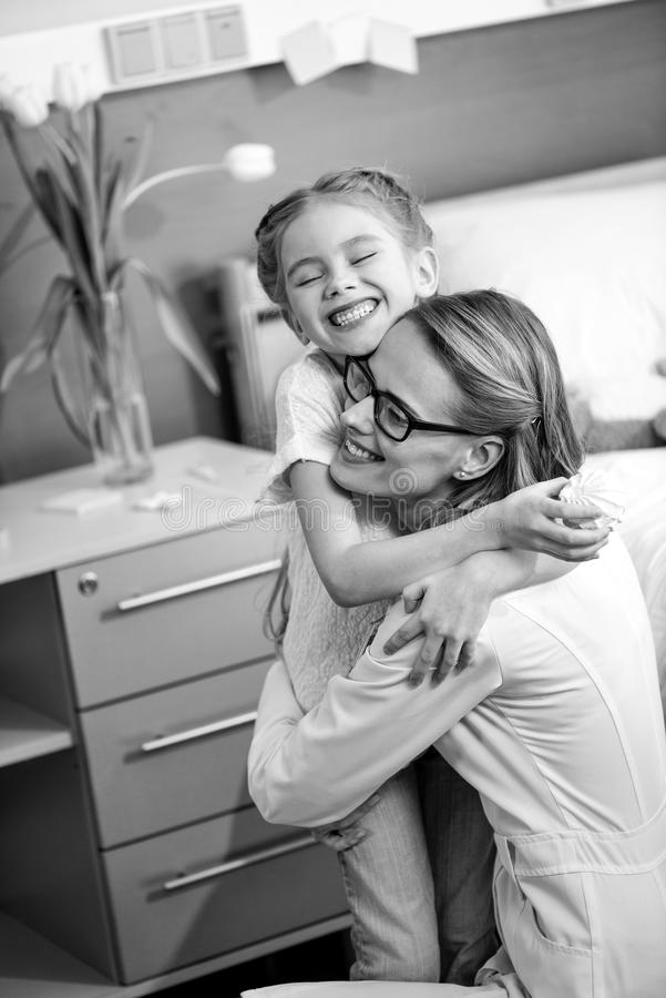 Happy woman doctor and little girl patient hugging in hospital room stock photo