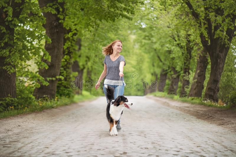Happy woman with dog on road royalty free stock photography