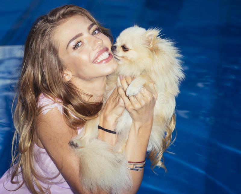 Happy woman and dog in pool. Happy woman and dog on summer vacation in pool royalty free stock image