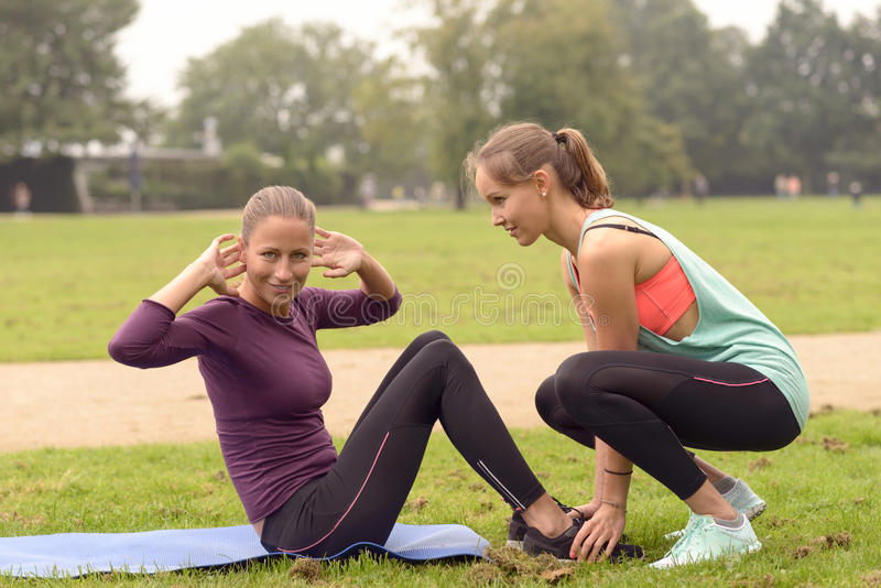 Happy Woman Doing Curl Up Exercise. Happy Athletic Woman Smiling at the Camera While Doing Curl Up Exercise at the Park with the Help of her Friend stock images