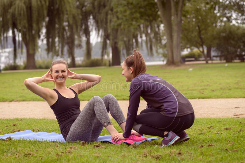 Happy Woman Doing Curl Up Exercise. Happy Athletic Woman Smiling at the Camera While Doing Curl Up Exercise at the Park with the Help of her Friend stock photos