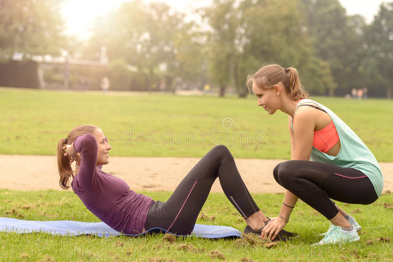 Happy Woman Doing Curl Up Exercise. Happy Athletic Woman Smiling at her friend While Doing Curl Up Exercise at the Park royalty free stock image