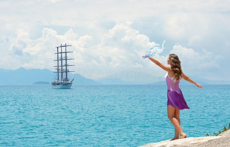 Happy woman in dress waving handkerchief on background of islands and sailing ship on summer sunny day stock image