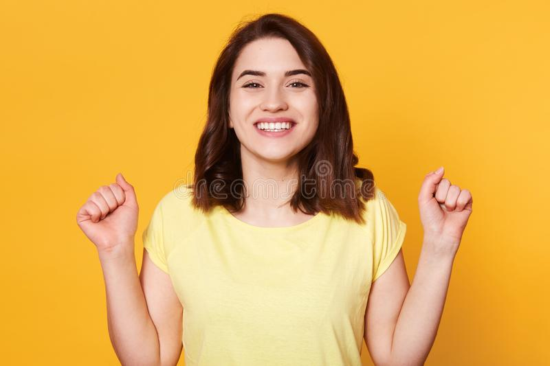 Happy woman dressed casual t shirt, clenching her fists with excitement, celebrating, achieving goal, her dreams come true, posing stock photos