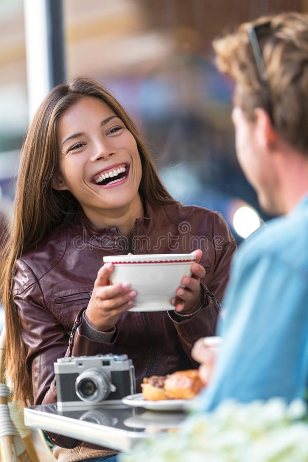 Happy woman drinking coffee at cafe. Asian girl, conversation with man friend laughing sitting at restaurant table having fun. stock photos