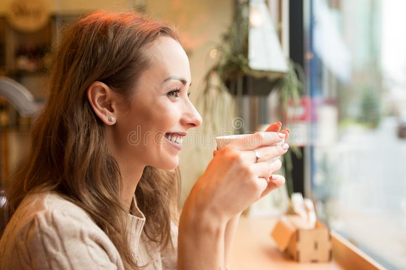 Happy woman drinking coffee in cafeteria stock image