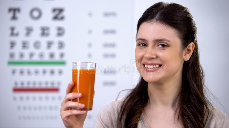 Happy woman drinking healthy fresh carrot juice, eye chart on background, vision royalty free stock image