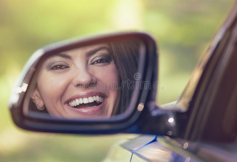 Happy woman driver looking in car side view mirror laughing royalty free stock photography