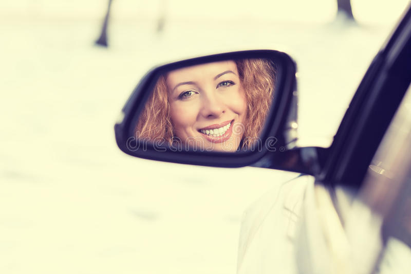 Happy woman driver reflection in car side view mirror. Safe winter trip, journey driving concept. Happy young woman driver reflection in car side view mirror royalty free stock photography