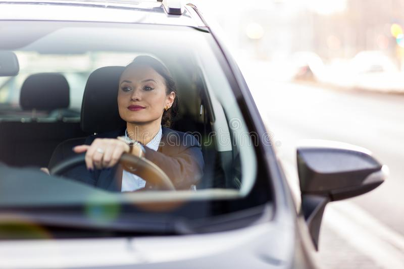 Woman driving a car and smiling royalty free stock photography