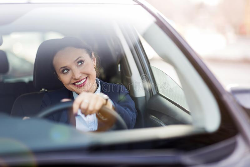 Woman driving a car and smiling stock image
