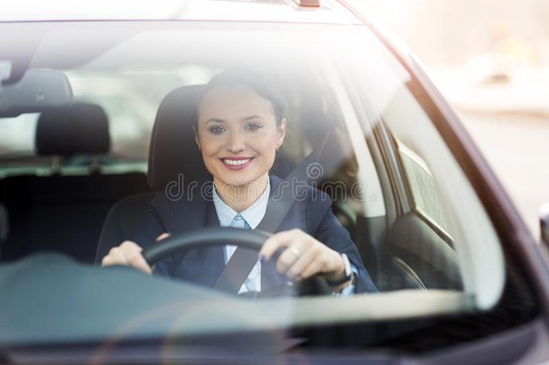 Woman driving a car and smiling stock photo
