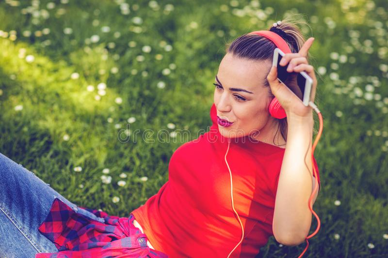 Happy woman with earphones and smartphone listening to music on royalty free stock photo