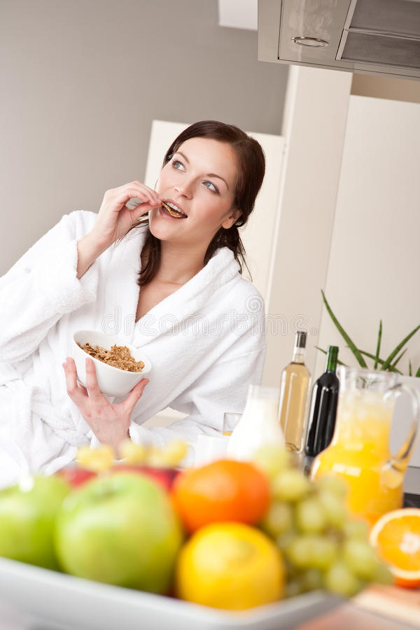 Happy woman eat cereals for breakfast in kitchen