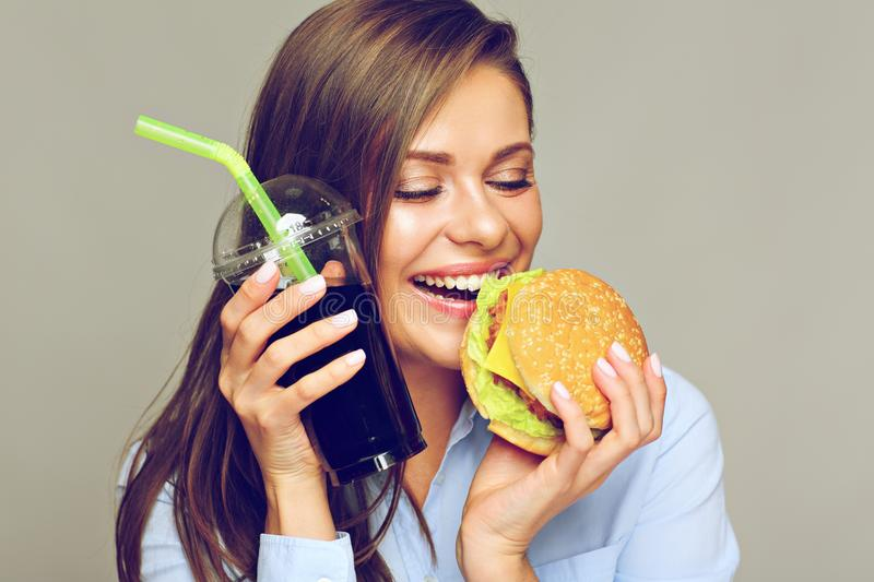 Happy woman eatin American classic fast food. Burger with cola stock photo