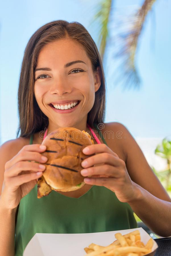 Happy woman eating burger sandwich at outdoor terrace bistro. Young Asian girl enjoying lunch meal at restaurant. Beautiful royalty free stock image