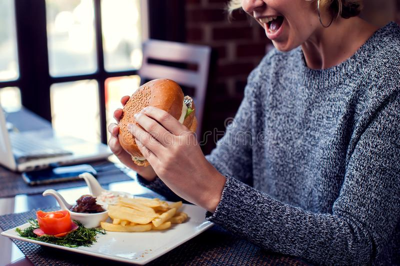 Happy woman is eating burger and smiling while spending time in cafe. People, food and entertaiment concept royalty free stock photo