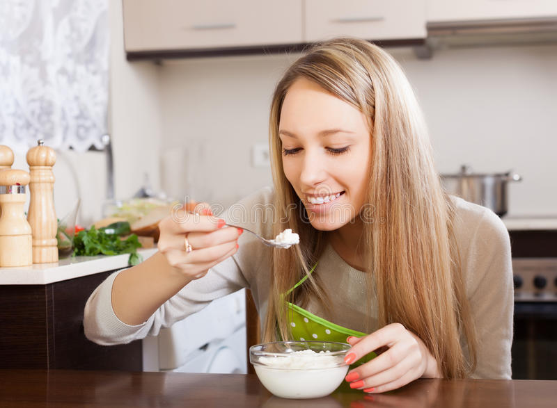 Happy woman eating cottage cheese. At table stock photos
