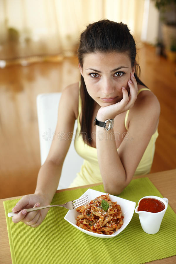 Happy woman eating pasta stock images
