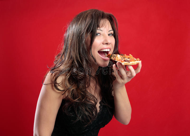 Happy woman eating pizza. A beautiful happy woman eating a slice of tasty italian pizza stock image
