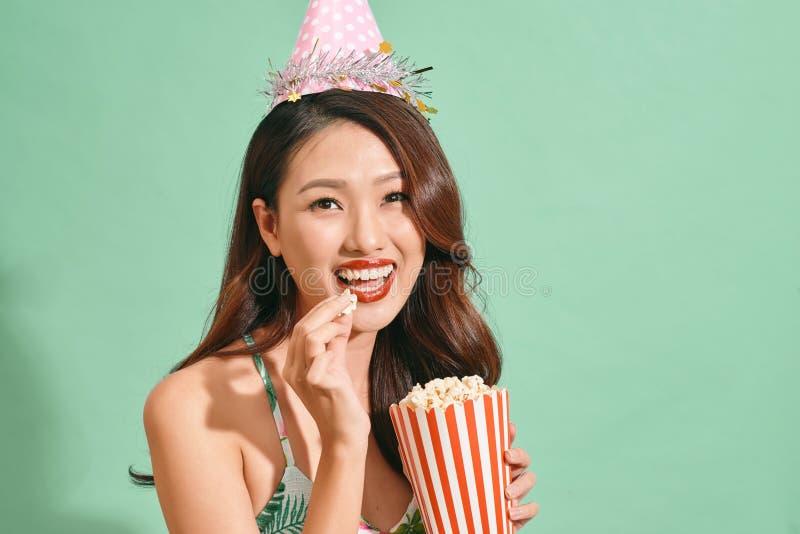 Happy woman eating popcorn on blue background.  stock photo