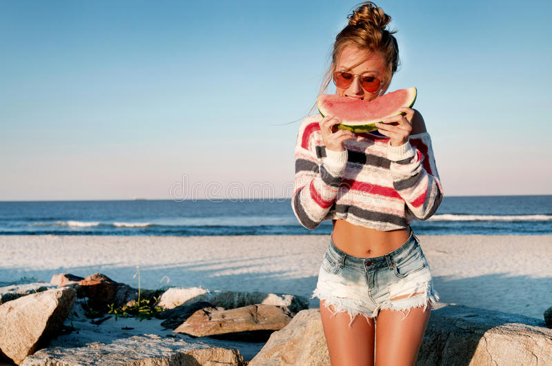 Happy woman eating watermelon on the beach. royalty free stock photo