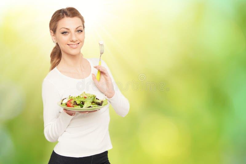 Happy woman eats healthy salad stock photography