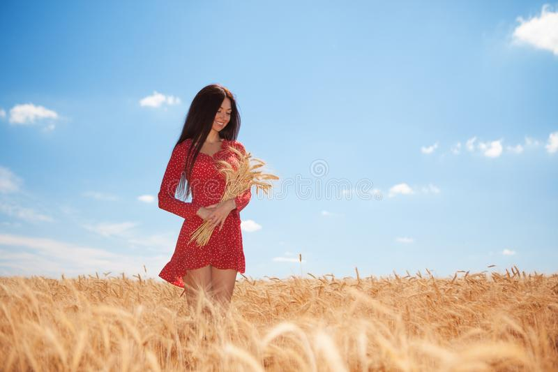 Happy woman enjoy the life in the field. Nature beauty, blue sky,white clouds and field with golden wheat. Outdoor lifestyle. stock photography